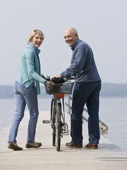 A senior couple pushing a bicycle along a wooden jetty