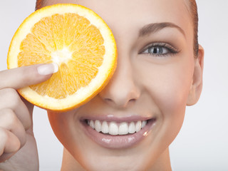 A woman holding a slice of orange in front of her eye