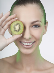 A woman holding a slice of kiwi fruit in front of her eye