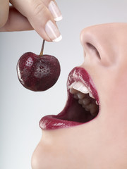 A woman eating a cherry, close-up