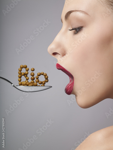 A woman eating bio cereal from a spoon, side view