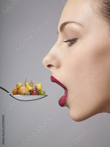 A woman eating fruit from a spoon, side view