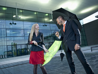 A man and a woman holding umbrellas in the rain