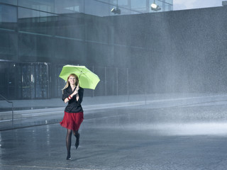 A young woman holding a green umbrella in the rain