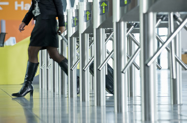 A woman wheeling her suitcase through ticket barriers