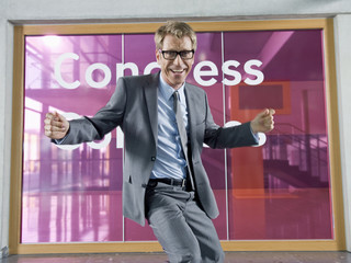 A mature businessman dancing in front of a congress centre
