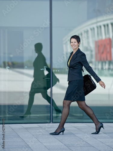 A businesswoman walking confidently along a street