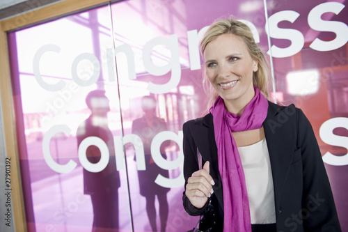 A portrait of a businesswoman standing outside a congress centre wearing a pink scarf
