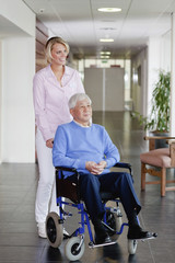 A care assistant pushing a senior man in a wheelchair