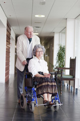 A senior man pushing his wife in a wheelchair