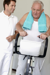 A senior man on an exercise bike, physiotherapist by his side