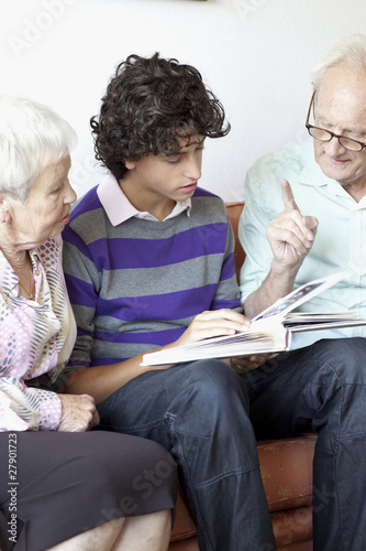 Grandparents and grandson looking at a photograph album together