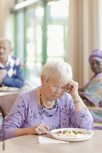 A senior woman having lunch looking sad