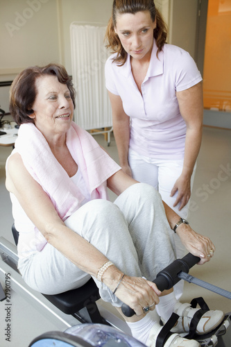 A senior woman working out on a rowing machine, fitness instructor at her side