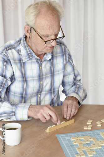 A senior man playing a board game
