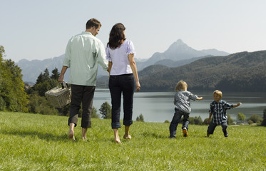 A family walking through the grass, children playing