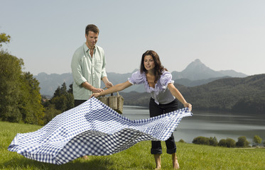 A couple laying a picnic blanket on the grass
