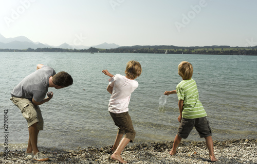 Three children skimming stones