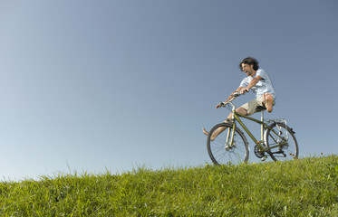 A man freewheeling downhill on a bicycle in summertime