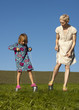 A mother and daughter playing outside on tin can stilts
