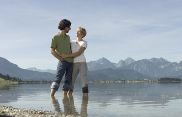 A couple standing in a mountain lake in summer