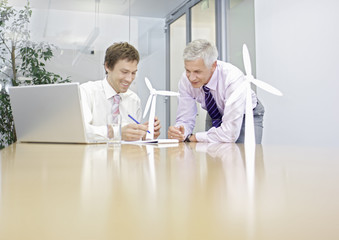 Two businessmen discussing wind turbine technology