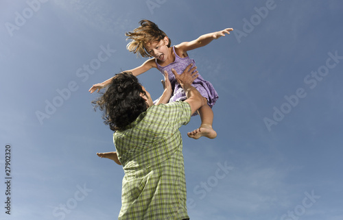 A father throwing his daughter in the air