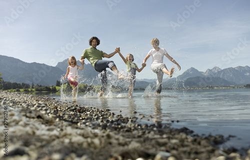 A family paddling in a lake, kicking the water