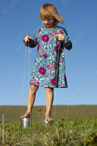 A girl playing outside on tin can stilts
