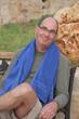 Mann mit blauem Handtuch um den Hals auf Bank sitzend