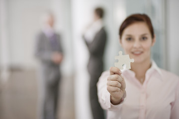 A businesswoman holding a piece of a jigsaw, two businessmen in the background