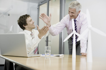 Two businessmen sitting in an office with model wind turbines celebrating success