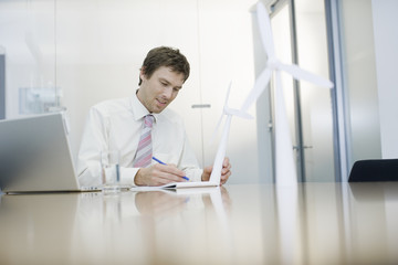 A businessman sitting at a desk holding a model wind turbine, making notes