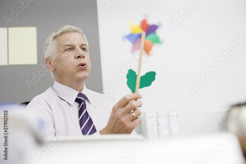 A mature businessman sitting at a desk blowing a toy windmill