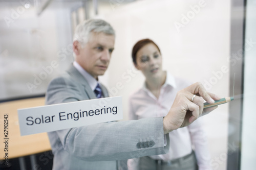 A businessman demonstrating a solar engineering project to a colleague