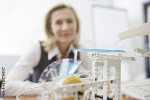 A businesswoman looking at a model of a water wheel