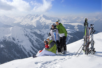 Family sitting in snow on mountain top with skis