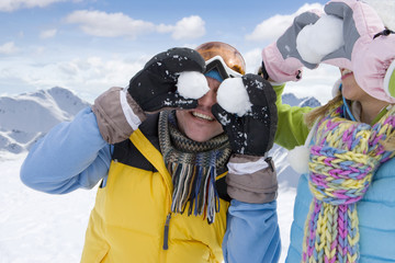 Man and woman holding snowballs in front of their eyes