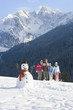 Family with sled standing on ski slope near snowman