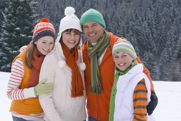 Family in caps and scarves standing together in snow