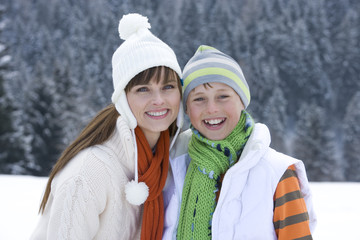 Mother and son in cap and scarf smiling together in snow