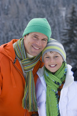 Father and son in cap and scarf smiling together outdoors