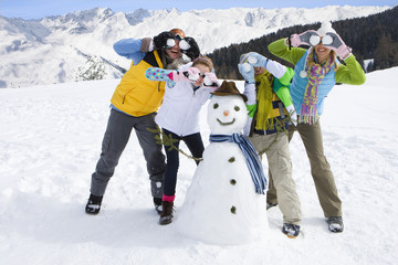 Family standing near snowman with snowballs covering their eyes