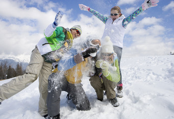 Family having snowball fight on ski slope