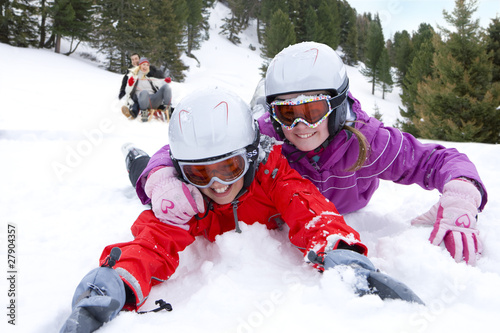 Brother and sister laying in snow on ski slope