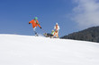 Father pulling family on sled on ski slope