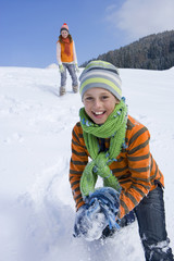 Brother and sister having snowball fight on ski slope