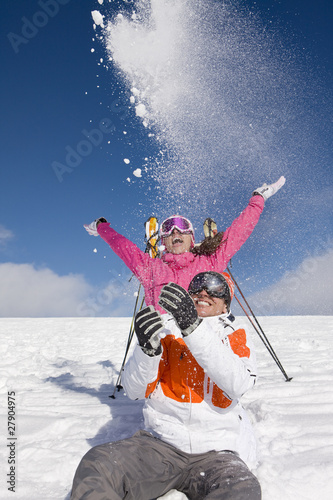 Skiers throwing snow on ski slope