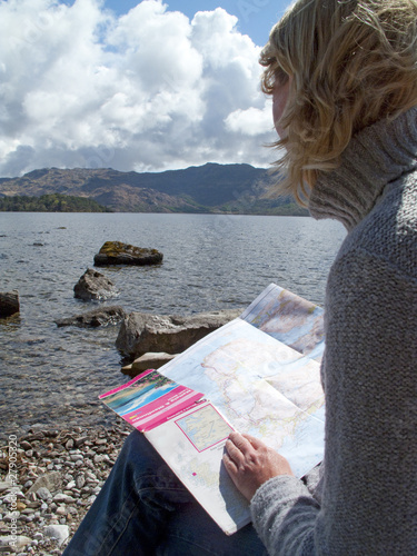 Woman looking at map and sitting rocky shore of lake