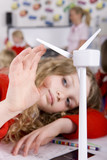 Serious school girl spinning model wind turbine in classroom